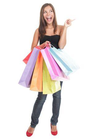 mujer cuerpo completo: Comprador apuntando al espacio de copia. Imagen de longitud completa aislado sobre fondo blanco, mostrando a una hermosa mujer de compras excitada.  Foto de archivo