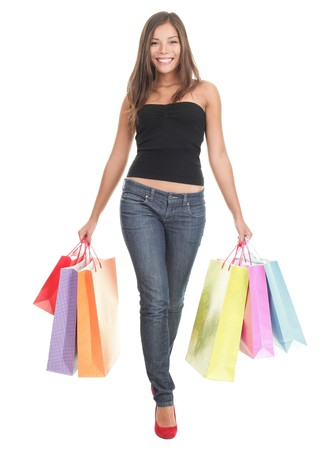 Shopping woman walking holding shopping bags - isolated in full length on white background. Beautiful multiracial Chinese Asian  Caucasian young woman model in her 20s.  photo