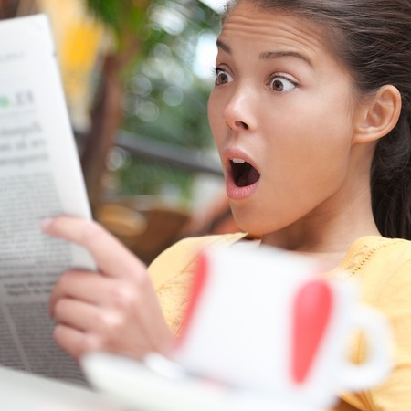 newspaper read: Woman shocked over shocking news in newspaper (gossip, stock market...). Young woman reading the paper on cafe outside. Stock Photo
