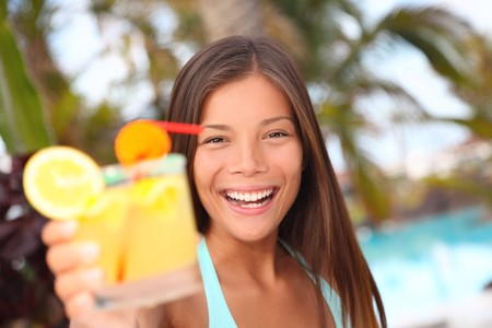 Woman with tropical drink by the pool tropical resort. Beautiful multiracial Asian  Caucasian young woman in bikini during summer holidays. photo