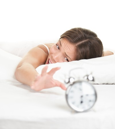 Woman and Alarm Clock. Funny image of woman lying in bed early in the morning. Isolated on white background. photo