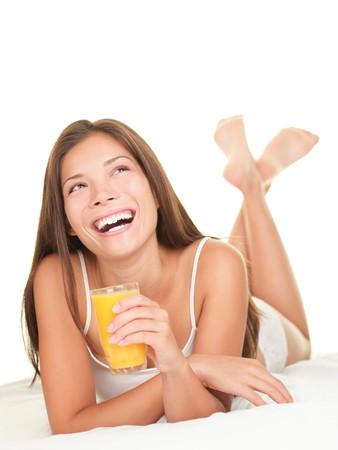 jus orange glazen: Vrouw in bed drinken sinaasappel sap bij het ontbijt. Mooie Aziatische  Kaukasische model liggen van volledige lengte geïsoleerd op witte achtergrond