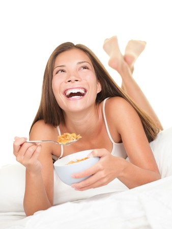 Woman eating breakfast in bed. Happy woman enjoying cornflakes cereals in the bed in the morning. Beautiful mixed race Chinese Asian  Caucasian female model lying in bed isolated on white background.