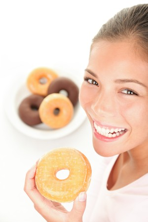 Donuts. Woman eating donut smiling on white background   photo