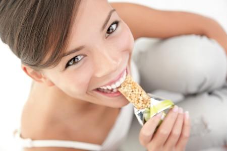 barre de c�r�ales: Jeune femme asiatique caucasien manger sain muesli barre.