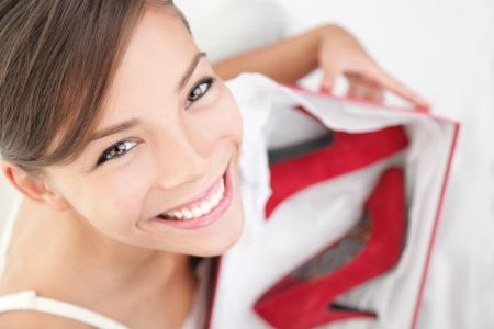 sapato: Woman getting shoes as gift or happy of her shopping. Asian woman surprised and happy to receive red high heels shoes as a present. Isolated on white.