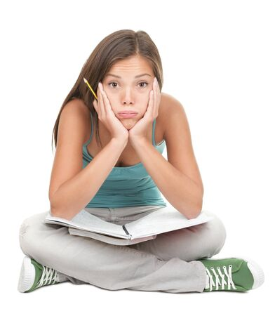 University student bored, frustrated and overwhelmed by studying homework. Young woman sitting down on floor isolated on white background. Stock Photo - 7439197