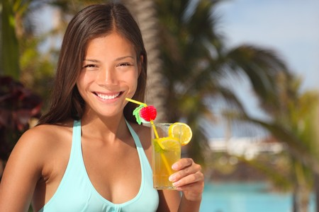 Resort woman drinking tropical drink outside by the pool at a tourist resort. photo