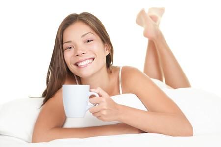 mujer tomando cafe: Mujer en la cama, beber t�. Mujer goza de t� en la cama en la ma�ana. Hermosa raza mixta China Asia  cauc�sica modelo femenino en la cama aislado sobre fondo blanco.