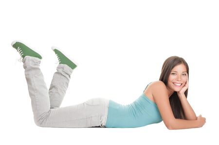 lying down on floor: Female university student lying down on the floor isolated on white background. Happy beautiful casual young multiracial Asian  Caucasian woman smiling at camera while relaxing.