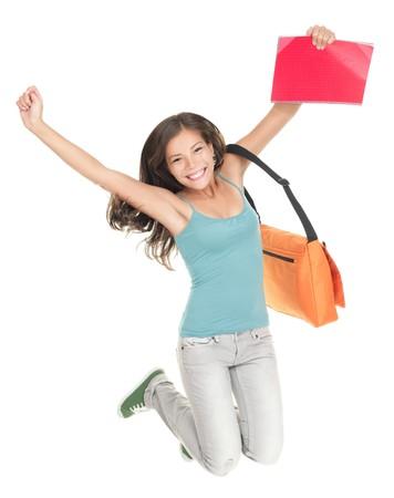 大学生の白い背景で隔離のジャンプ。美しい笑顔混血白人中国語の若い女性モデル