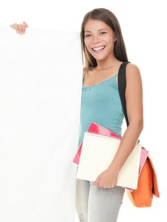 学生の標識です。空白の空のビルボードの兆しを見せ美しい大学大学生の笑みを浮かべてください。美しい若い混血アジアコーカサス地方女性は白 写真素材