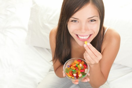 Gummy: Candy woman eating sweets with a fresh smile in bed - copy space. Top view of Mixed Chinese Asian  Caucasian young female model. Stock Photo