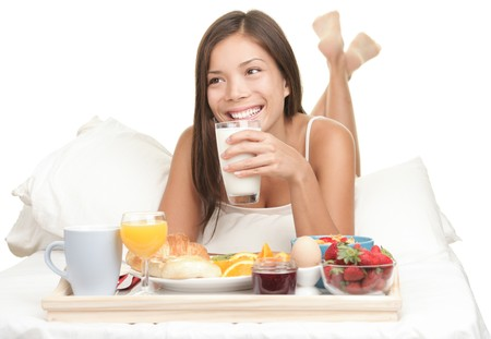 Breakfast woman enjoying milk and eating continental breakfast from tray in bed - Smiling looking away. Bed and woman isolated on white background