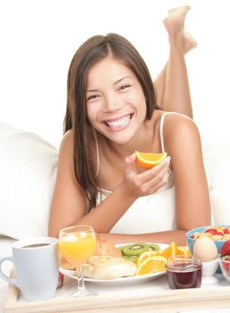 dentudo: Mujer toma el desayuno en la cama. Gran sonrisa pez. Mujer de raza blanca y asi�tica aislada sobre fondo blanco  Foto de archivo