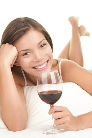 Red wine. Woman drinking red wine in bed. Asian-Caucasian female model. White background. photo
