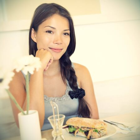 Woman at cafe thinking happy and smiling. Young beautiful Caucasian  Asian female model. Image is cross-processed giving retro style.