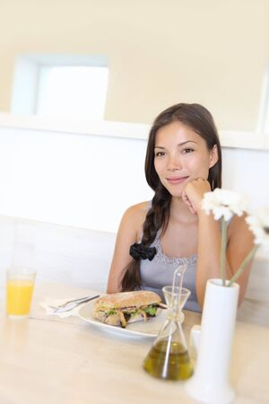 Cafe woman smiling. Asian woman eating at coffee shop. Pensive cheerful young female model. Stock Photo - 7780025