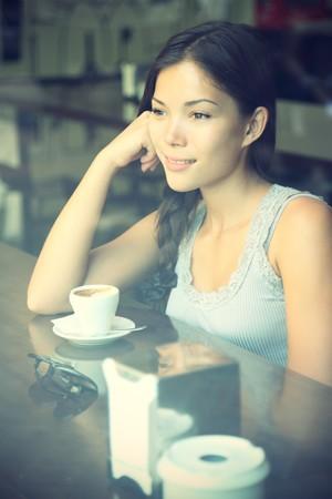 カフェ。コーヒーを飲む窓カフェ思考の女性。若い美しいアジアコーカサス地方モデル。クロス処理イメージ。 写真素材