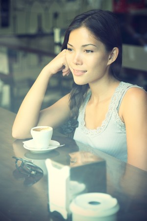 Cafe. Woman at cafe thinking looking out the window drinking coffee. Young beautiful Caucasian  Asian model. Cross processed image. photo