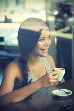 トレンディなカフェ コーヒーを飲む女性。若い美しいアジアコーカサス地方モデル。Windows からの反射。クロス処理画像。 写真素材