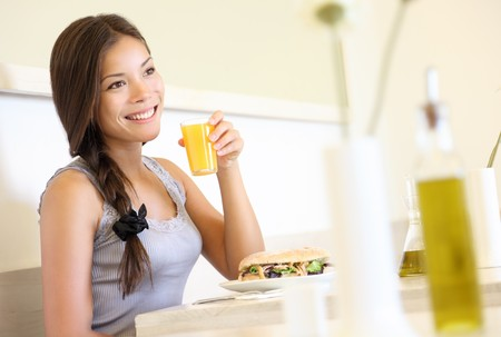 Cafe woman drinking orange juice eating a sandwich inside in bright beautiful cafe. Asian  Caucasian young female model. Stock Photo