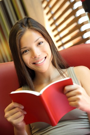 Woman reading a book at home. Young beautiful Caucasian  Asian female model photo