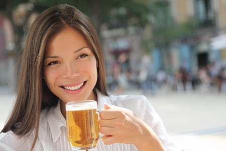 beer drinking: Woman drinking beer on sidewalk cafe. Beautiful young mixed race asian  caucasian female model smiling enjoying the city life at a town square. Stock Photo