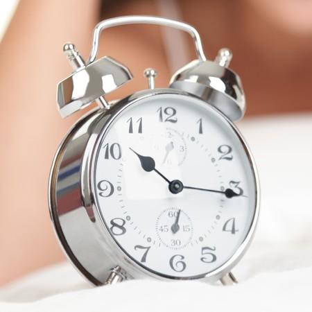 Alarm klok. Vrouw in bed in de achtergrond. Laat voor het werk?
