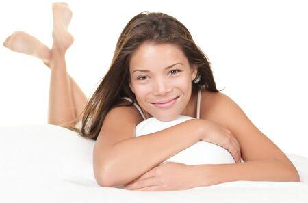 pijama: Hermosa mujer acostada en la cama de relajaci�n y sonriente de una c�mara. Hermoso chino  modelo femenino del C�ucaso en blanco.  Foto de archivo