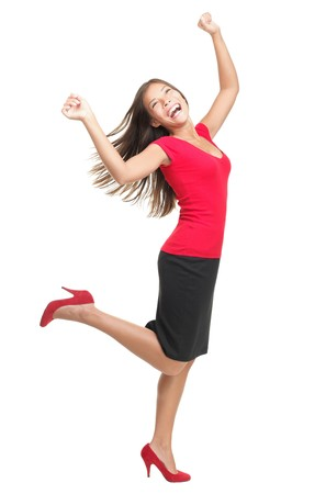 Ecstatic woman dancing and celebrating. Excited happy and joyful asian businesswoman isolated in full length on white background. Casual mixed caucasian  chinese female model in red. Stock Photo