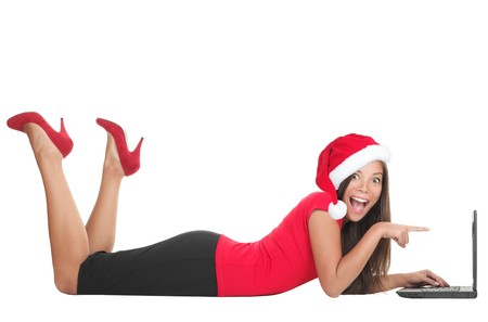 buying: Christmas internet shopping. Woman excited about buying gifts online or winning something on her laptop. Young woman lying down in full length on the floor isolated on white background.