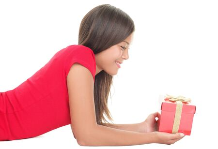 Woman holding gift lying down isolated on white. Smiling happy girl looking at birthday / christmas / valentines present. Stock Photo - 7780064