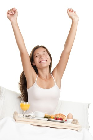 Happy woman stretching in bed in the morning with breakfast tray. Asian  Caucasian woman on white background.