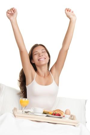 despertarse: Mujer feliz que se extiende en la cama en la ma�ana con una bandeja de desayuno. Asia  cauc�sica mujer sobre fondo blanco.