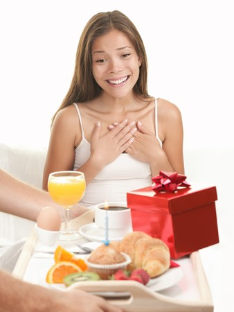 Couple having romantic morning in bed - woman surprised by breakfast and gift  present. Use for Valentines day, birthday, romantic relationship concept or? Beautiful young mixed Asian  Caucasian model in bedroom isolated on white background.  photo