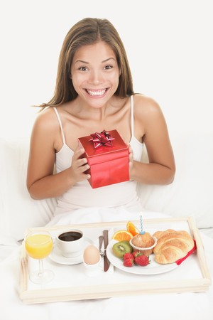 Birthday gift woman getting morning surprise in bed with present and breakfast. Young smiling excited and happy woman holding a birthday gift or a valentines day present.  photo