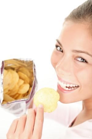 merenda: I gettoni. Donna che mangiava il sacchetto di patatine  patatine - sorridente felice guardando fotocamera. Bella giovane Caucasian  asiatica femmina modello.  Archivio Fotografico