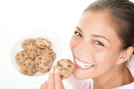 Cookie woman eating chocolate chip cookies. Cute young mixed race chinese / caucasian model on white background.