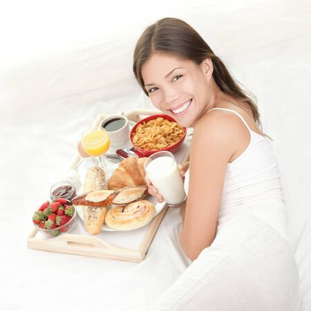 Breakfast in bed. Young woman eating breakfast in bed drinking milk. Beautiful young woman smiling.