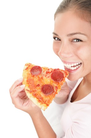 Woman eating pizza on white background smiling looking at camera. Portrait of young mixed asian  caucasian woman model.