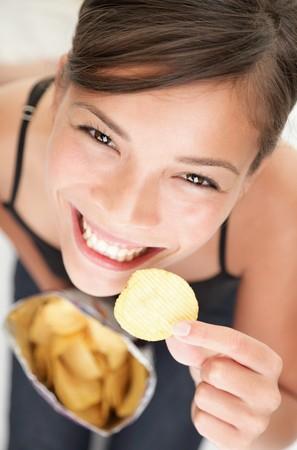 merenda: Donna che mangiava chip. Bella donna giovane mangiare patate chip  patatine.