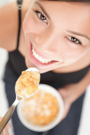 Cornflakes cereals. Woman eating cornflakes. Cute mixed race young Chinese  white Caucasian model in high angle view eating breakfast.  photo