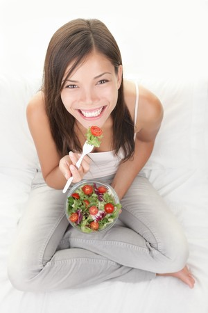 Woman eating salad. Beautiful healthy smiling mixed Asian Caucasian woman enjoying a fresh healthy salad sitting in bed looking up. High angle view with copy space on white background. Banque d'images
