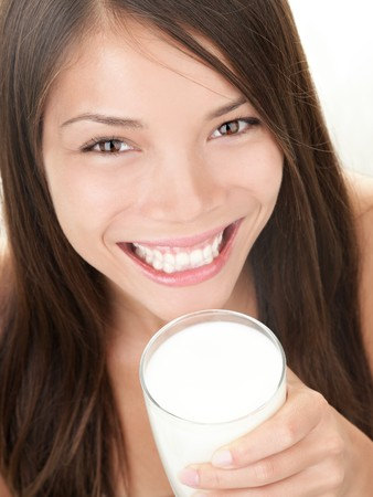 woman drinking milk: Milk - Woman drinking milk. Happy smiling beautiful young woman enjoying a glass milk while smiling looking at camera Stock Photo