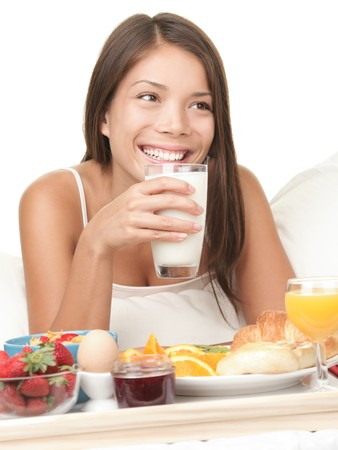 Woman eating breakfast in bed drinking a glass of milk. Morning photo of beautiful natural mixed race Chinese  White Caucasian female model smiling looking away photo