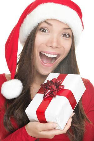 Christmas woman showing gift wearing Santa hat. Santa woman portrait of a cute, beautiful smiling mixed race Asian / Caucasian model. Isolated on white background.  Stock Photo - 7989986