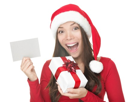 Christmas woman smiling excited holding gift and blank sign with copy space. Beautiful young smiling woman in Santa hat showing white paper card sign. Caucasian  Asian model isolated on white background.  photo