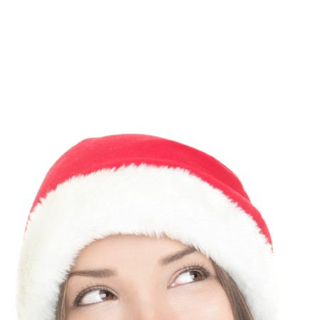 Christmas woman looking upwards at copy space. Closeup of santa girl looking up at white space. Mixed Asian  Caucasian woman. photo