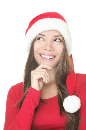 Santa hat woman thinking and looking up isolated on white background. Close up of smiling Asian Caucasian female model wearing red. photo